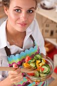 Young woman eating fresh salad in modern kitchen