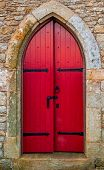 Old Red Wooden Church Door On Stone Wall