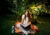 picture of night gown  - Young smiling woman sitting at night in garden and reading big old book - JPG