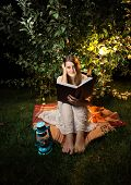 stock photo of night gown  - Outdoor shot at night of woman reading book at light of garden lantern - JPG