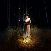 pic of fireflies  - Beautiful woman in long dress reading big old book at mysterious forest with fireflies - JPG