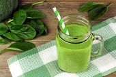 picture of smoothies  - Healthy green smoothie with spinach in a jar mug with checkered cloth against wood - JPG