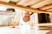 stock photo of pity  - Portrait of little smiling girl looking under bed - JPG