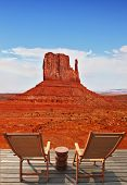 Red sandstone in the valley of the Navajo, USA. Two wooden deck chairs on the platform are to review the rock -
