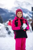 pic of snowball-fight  - Beautiful smiling girl in pink ski suit making snowball - JPG
