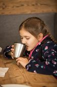 pic of thermos  - Closeup portrait of cute girl drinking tea from thermos at cafe - JPG