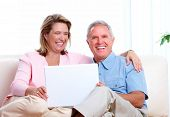 Senior couple looking information at home with computer.