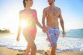 Mixed race couple walking holding hands happily smiling at beach sunset waterfront, enjoying summer honeymoon travel vacation. Hawaii