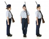 A profile, front and face right view of a Jr. ROTC teen in uniform with her rifle.  On a white background.