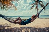 Woman Relaxing In Hammock On Tropical Beach