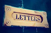 Brass letter box in old painted door, close-up, toned image