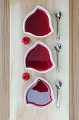 Strawberry jam (sweet) in a bowls on dark red background with tablespoons