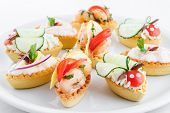 Assortment of salty mini tartlets stuffed with vegetable, shrimps and cream cheese