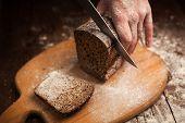 foto of fresh slice bread  - Male hands slicing fresh bread on wood table  - JPG