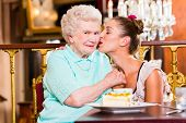 Senior woman and granddaughter with cake in old fashioned cafe