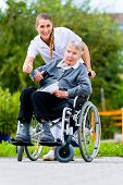 image of nursing  - Senior woman in nursing home with nurse in garden sitting in wheelchair giving the thumbs up sign - JPG