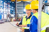picture of forklift driver  - Worker and forklift driver in industrial factory looking at camera - JPG