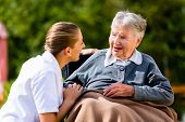 stock photo of nursing  - Nurse holding hands with senior woman sitting in wheelchair in garden of retirement home - JPG