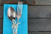 Silverware tied with rope on colorful napkin and wooden planks background