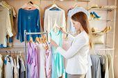Beautiful young shopper choosing dress in boutique