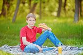Handsome boy in casual clothes eating sandwich on green lawn