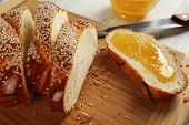 Sliced fresh bun with honey on cutting board on wooden table close up