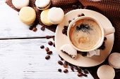 Gentle colorful macaroons and  coffee in mug on color wooden  background