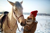 Happy girl in winterwear looking at horse in rural environment