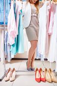 Elegant woman choosing new stylish dress and shoes