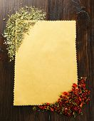 Spices on blank paper sheet on wooden background