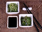 Seaweed salad with say sauce on wicker mat background