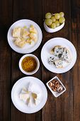 Various types of cheese on plates with  snacks on saucers on wooden table background
