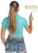 Woman holding paint roller. Rear view