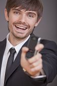 Laughing Businessman Showing Cell Phone