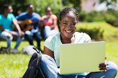 pretty female afro american college student with laptop computer outdoors
