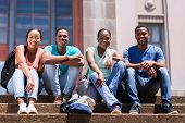stock photo of school building  - group of happy african student sitting outside college building - JPG