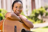beautiful young african woman with a guitar sitting outdoors