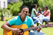 handsome male african college boy playing guitar