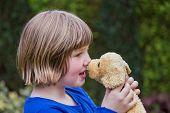 Young girl hugging stuffed dog