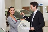 Smiling businessman giving car key to happy customer at new car showroom
