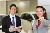 Female driver showing a key after bying a new car at new car showroom