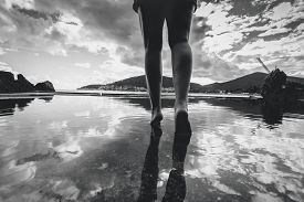 stock photo of reflections  - Black and white photo of female legs walking on water with sky reflecting on it - JPG