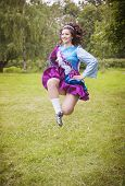 image of wig  - Young beautiful girl in irish dance dress and wig jumping outdoor - JPG