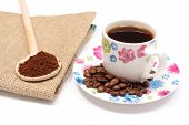 pic of coffee grounds  - Ground coffee on wooden scoop lying on jute canvas and cup of black coffee with coffee grains - JPG