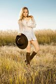 stock photo of tallgrass  - Sunrise shot of a pretty young model on meadow