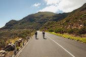 stock photo of triathlon  - Rear view of two cyclist riding down the country road through mountains - JPG