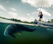 picture of fish pond  - Young man fishing from the boat in the pond - JPG