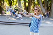 picture of pulling hair  - Woman with curly hair pulls soap bubbles in park - JPG