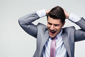 stock photo of disappointment  - Portrait of a disappointed businessman over gray background - JPG