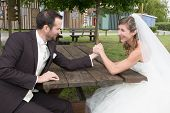 pic of wrestling  - Young happy newly wed couple fighting in arm wrestling - JPG